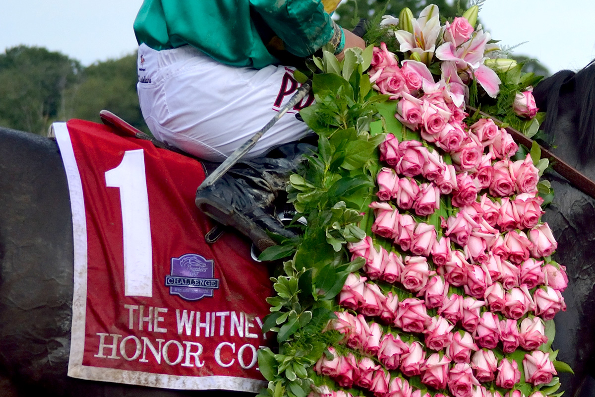 Honor Code wears the Whitney winner's garland of Marylou roses