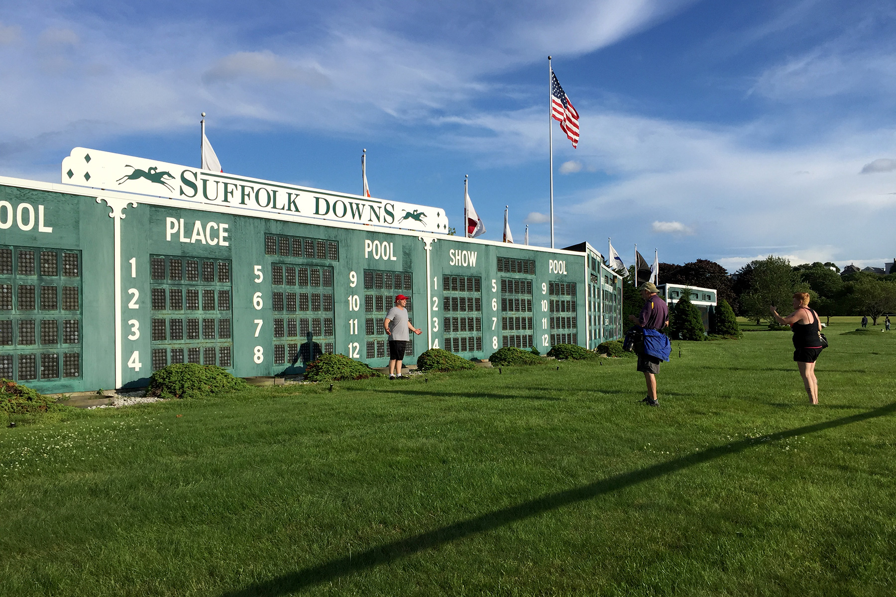 People cross the track to take their photos in front of the infield tote board